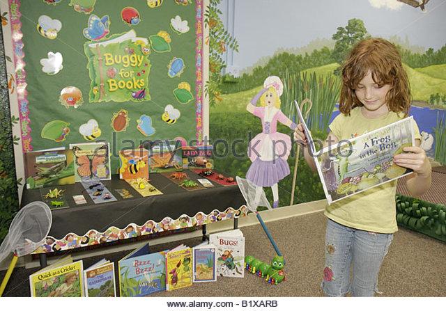 Arkansas Pocahontas Randolph County Library girl redhead elementary school reading children's books mural Little - Stock Image