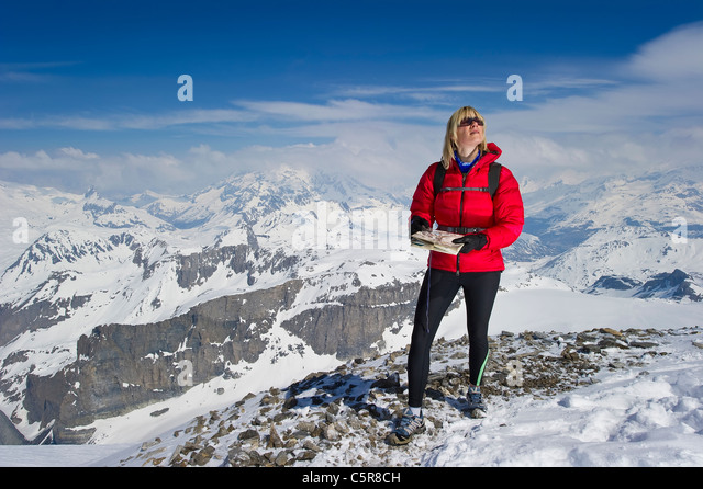 A women in high snowy mountains using a map and compass for orienteering. - Stock-Bilder