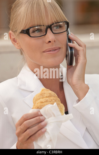 Business woman on the phone with pastry - Stock Image