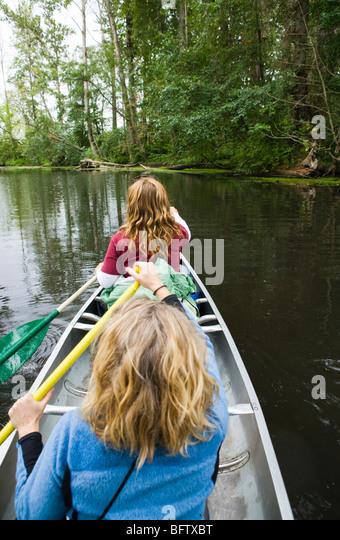 Two women paddling a canoe in the Washington State University Arboretum in Seattle, Washington, USA. - Stock-Bilder