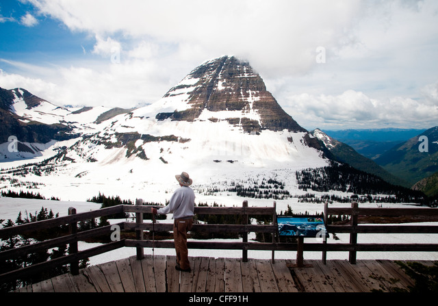 An older man stands at an overlook as peaks with snow rise in the background. - Stock Image