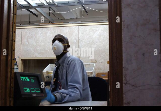 July 30, 2002 - .10/25/2001.POSTAL WORKER.WEARING MASK AND GLOVES TO PROTECT HIMSELF .FROM POSSIBLE ANTHRAX CONTAMINATION. - Stock Image