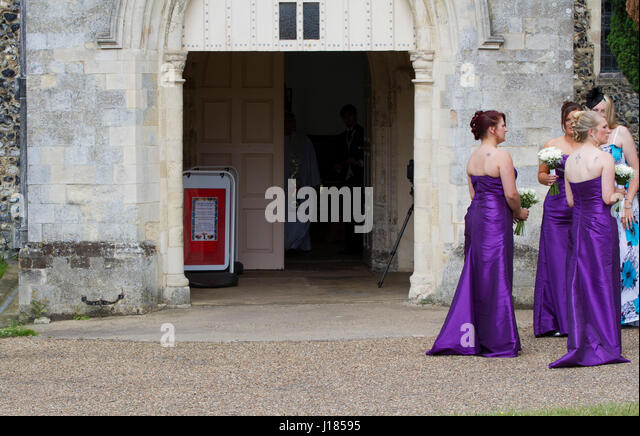Three bridesmaids in purple dresses wait for the bride - Stock Image