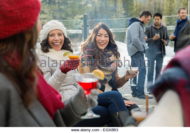 Friends in warm clothing drinking on patio - Stock Image