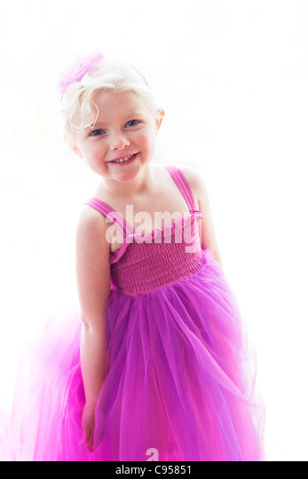 Smiling young girl wearing pink dress. - Stock Image