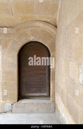 Wooden aged vaulted ornate door and stone wall at caravansary (Wikala) of Bazaraa, Medieval Cairo, Egypt - Stock Image