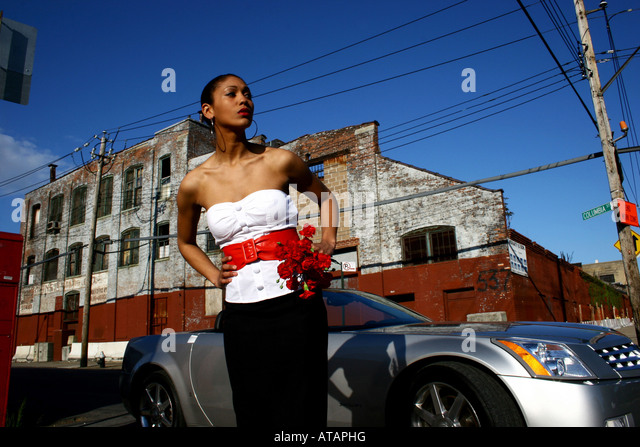 SOPHISTICATED YOUNG WOMAN HOLDING FLOWERS.  CONVERTIBLE CADILLAC CAR IN THE BACKGROUND. - Stock Image
