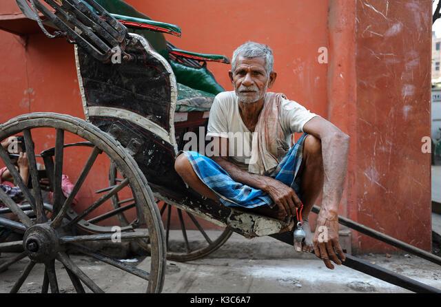 26.02.2011, Kolkata, West Bengal, India, Asia - A rickshaw puller waits for passengers at a roadside in Kolkata. - Stock Image