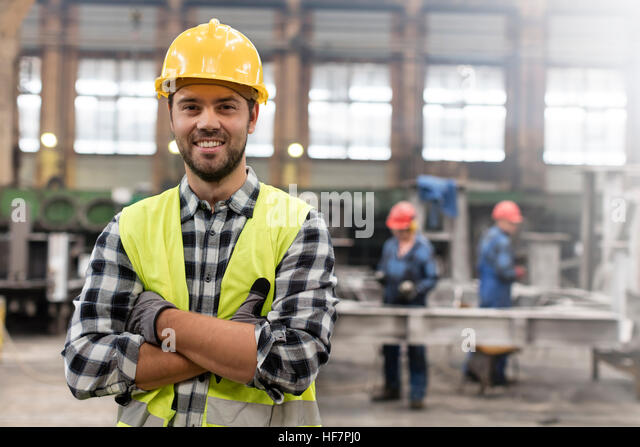 Portrait smiling confident steel worker in factory - Stock Image