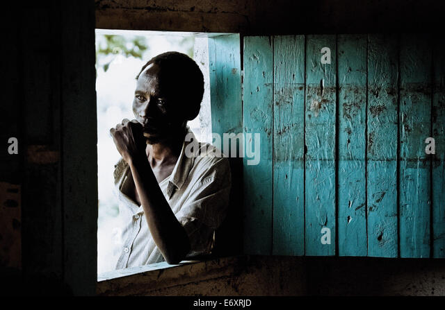 Man standing at the window of his hut, Uganda, Africa - Stock Image