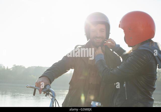 Young woman helping man put on crash helmet, smiling - Stock Image