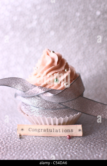 Pink cupcake on a silver grey bokeh background - Stock Image