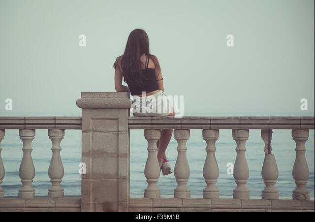 Rear view of a teenage girl sitting on a wall overlooking the sea - Stock Image