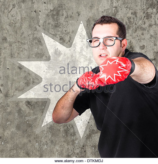 Regular guy punching and working up a sweat with boxing gloves on during a bootcamp fitness workout. Pow background - Stock Image