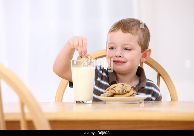 Young boy dipping cookie in glass of milk - Stock-Bilder