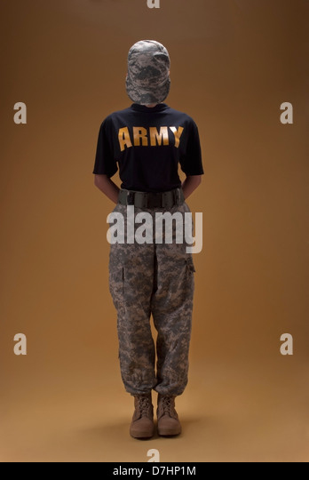 Young female wearing Woman's Army Combat (ACU) pants and Desert combat boots with a ACU camouflage hat covering - Stock Image