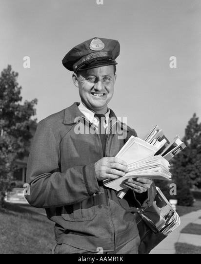 1960s SMILING MAILMAN OUTDOORS IN SUBURBAN NEIGHBORHOOD HOLDING LETTERS MAILBAG - Stock Image