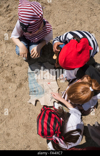 Directly above shot of children examining a treasure map in a adventure playground, Bavaria, Germany - Stock Image