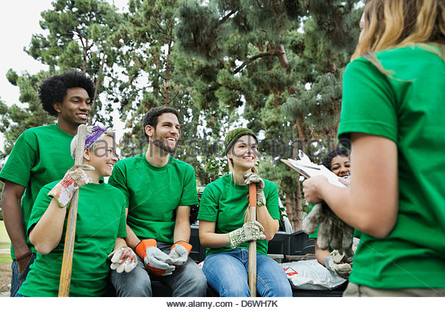 Group of happy environmentalists listening to female volunteer - Stock Image
