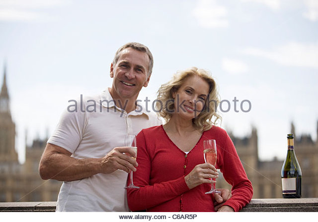 A middle-aged couple in front of the Houses of Parliament, holding glasses of champagne - Stock Image