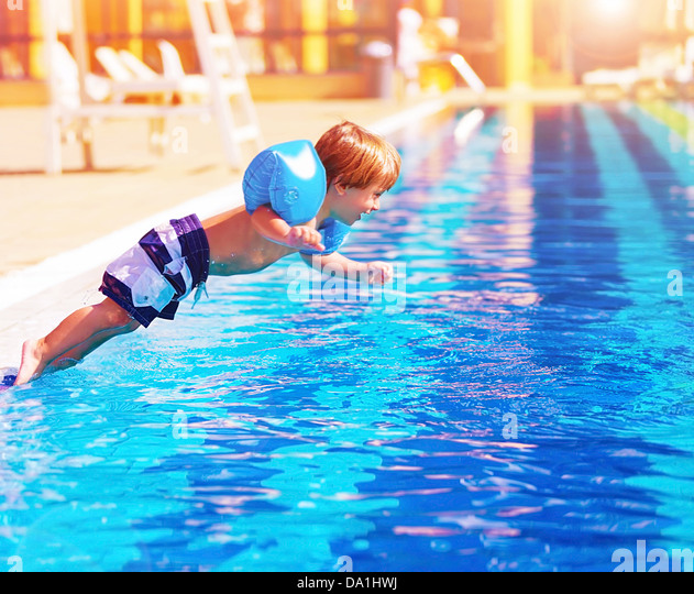 Adorable small boy jumping to the pool, having fun in aquapark, happy summer holidays, day care, active lifestyle - Stock Image