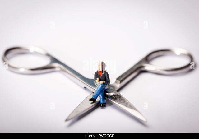 Vasectomy concept image of a miniature figure sat cross legged on a pair of scissors - Stock Image