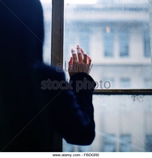 Rear View Of Woman Touching Glass Window - Stock Image