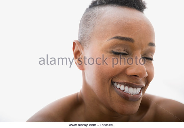 Close up of woman laughing with eyes closed - Stock Image