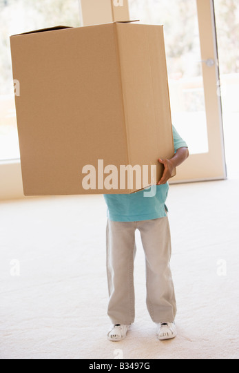 Young boy holding box in new home - Stock Image