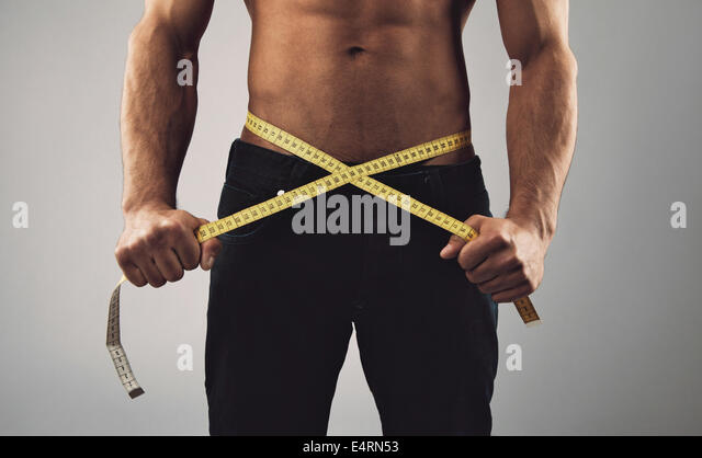Fitness man measuring his body. Cropped and mid-section image of young man measuring his waist with tape measure - Stock Image