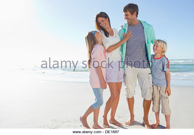 Happy family hugging on sunny beach - Stock Image