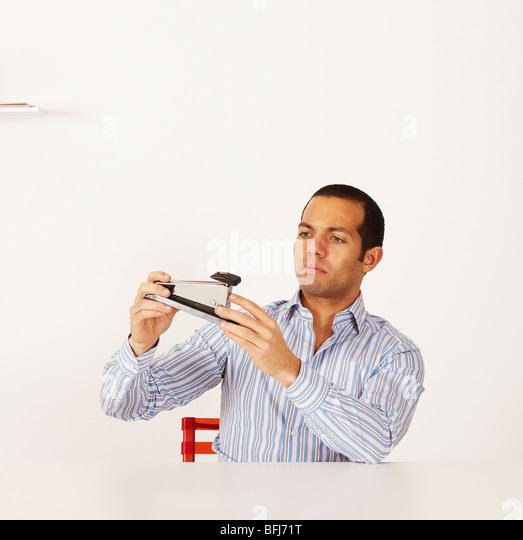 Man examining a stapler, Sweden. - Stock Image