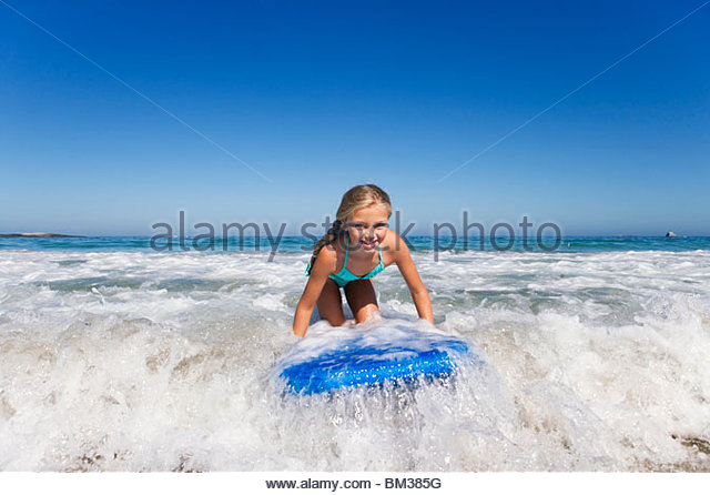 Smiling girl surfing on body board in ocean - Stock Image
