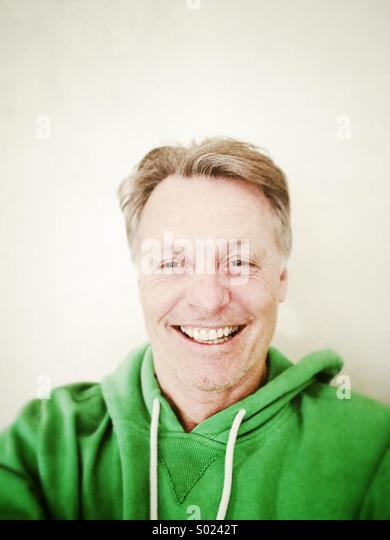 Happy smiling mature man in his forties wearing a green hooded top. - Stock-Bilder
