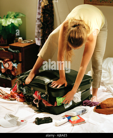 young woman standing on over packed suitcase in bedroom - Stock Image