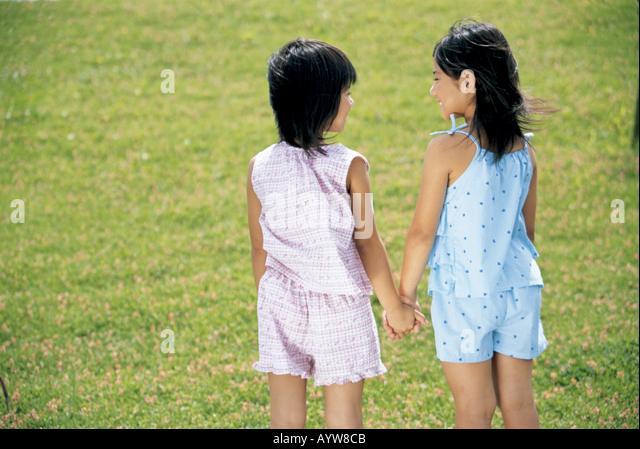 Two girls holding hands each other - Stock-Bilder