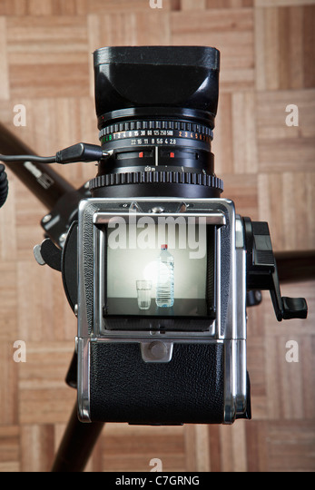 A medium format camera photographing a glass next to bottled water - Stock Image