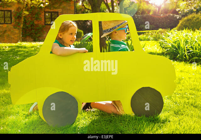Boy and Girl Kneeling behind Cardboard Cut Out in Shape of Car - Stock Image