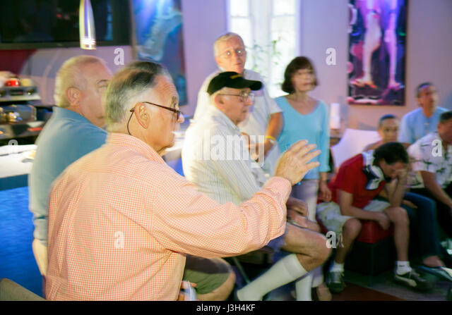 Miami Beach Florida Ocean Drive The Wave Hotel man men woman senior community meeting discussion speaks gestures - Stock Image
