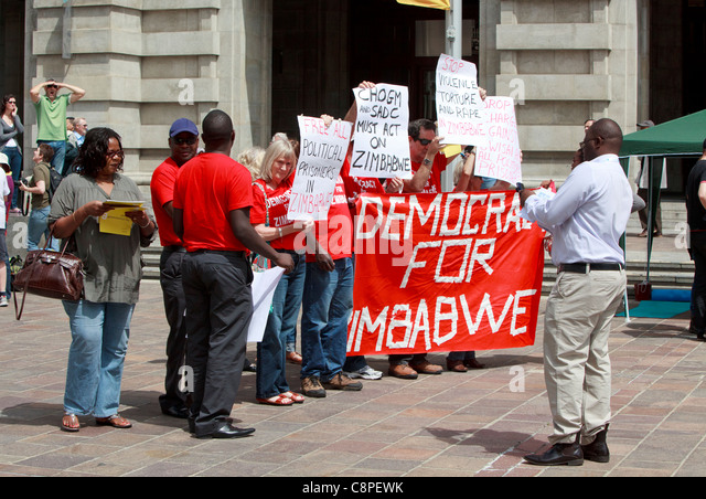 Anti Mugabe protesters holding a 'Democracy for Zimbabwe' banner at CHOGM 2011 protests in Perth. - Stock Image