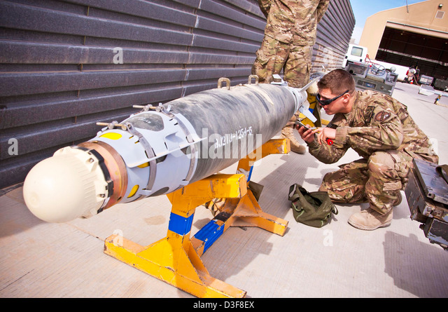 A US Air Force airman inspects a GBU-38 bomb before being loaded on a fighter aircraft February 11, 2013 at Kandahar - Stock Image