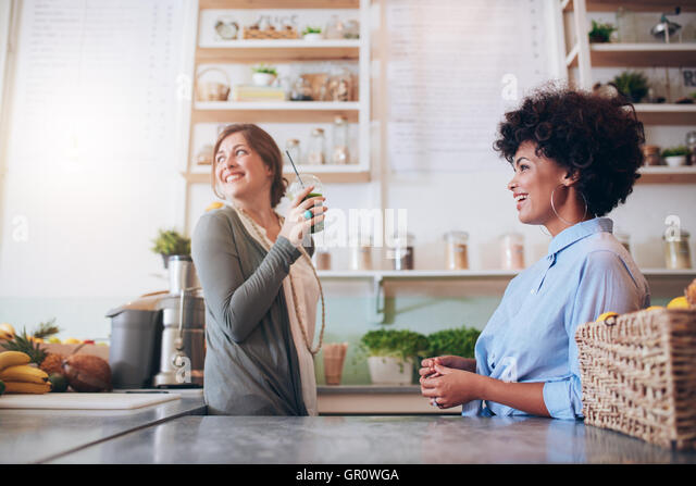 Two young female juice bar employees standing behind counter. Young women working at fruit juice bar. - Stock Image