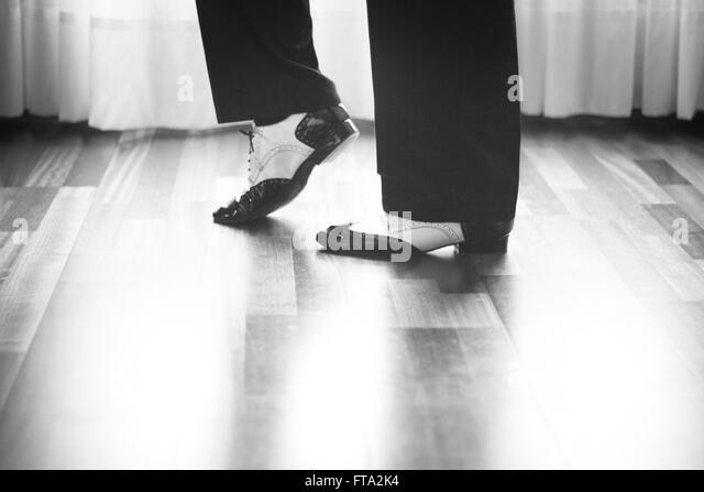 Male ballroom, standard, sport dance, latin and salsa dancer feet and shoes in dance academy school rehearsal room - Stock Image