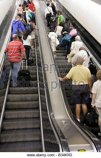 Atlanta Georgia Hartsfield-Jackson Atlanta International Airport escalator up ascend men women luggage side by side - Stock Image
