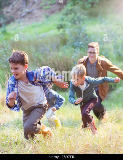 Boys running in field - Stock Image