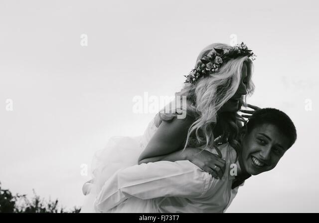 groom carries bride on his back outdoors - Stock-Bilder