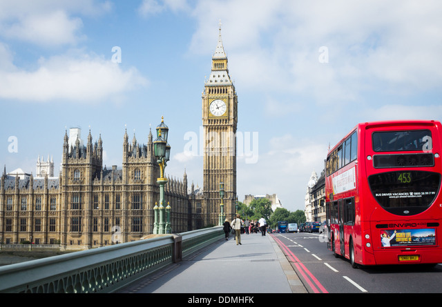 A London Bus driving over Westminster Bridge towards Big Ben and the Palace of Westminster - Stock Image