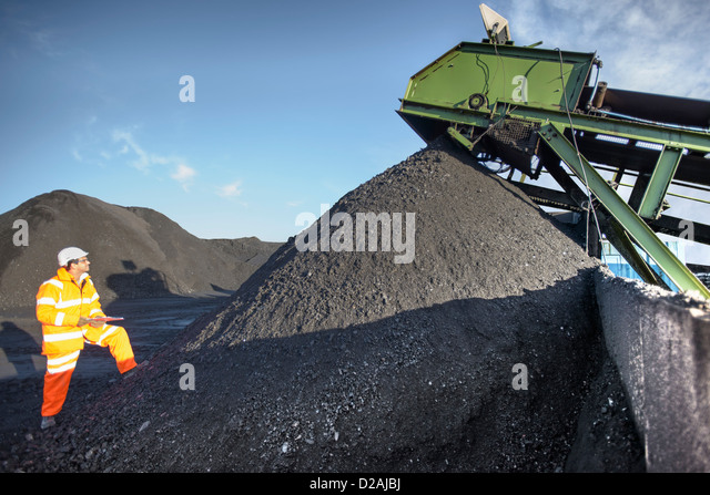 Worker examining pile of coal at mine - Stock Image