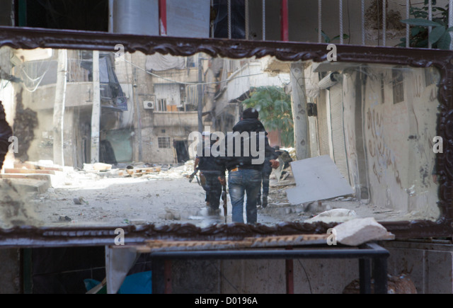 November 1, 2012 - Aleppo, Syria: Free Syrian Army fighters, selected in a mirror, walk towards the frontline. - Stock Image