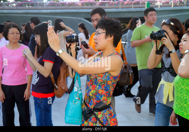 Singapore Singapore River Marina Bay Merlion Park Asian woman taking picture camera directing fashionable - Stock Image